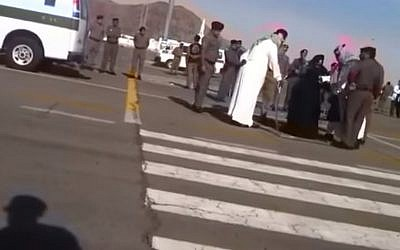 A woman is seen kneeling on the ground ahead of her execution in Saudi Arabi as a swordsman dressed in white stands above her, January 17, 2015 (Photo credit: YouTube screen capture)