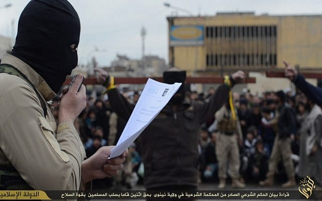 An Islamic State fighter reads the charges against two alleged thieves as they are seen crucified in the background (screen capture)