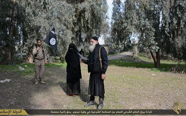 A woman in a niqab is led by Islamic State members to her stoning after being found guilty of infidelity (screen capture)