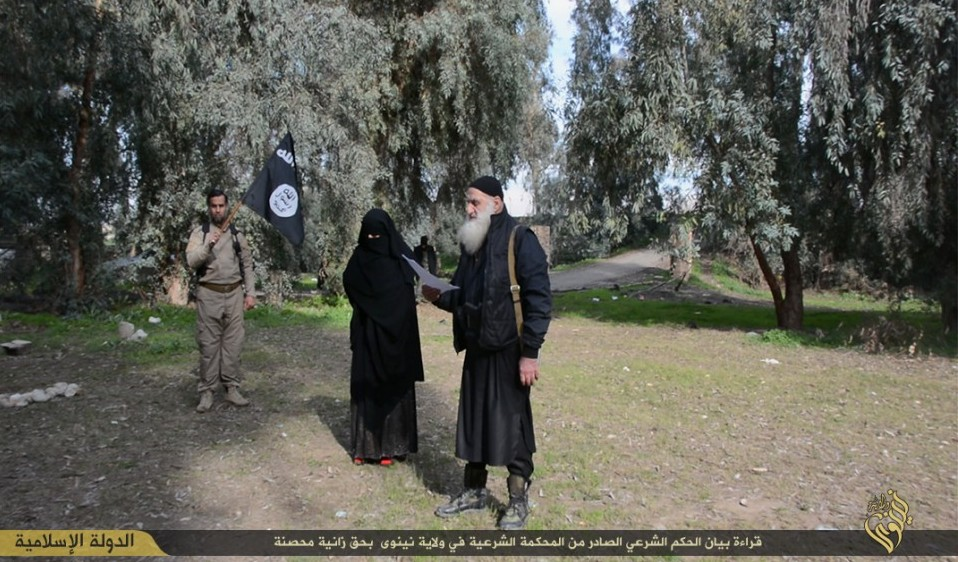 A woman in a niqab is led by Islamic State members to her stoning after being found guilty of infidelity (Photo credit: Courtesy)
