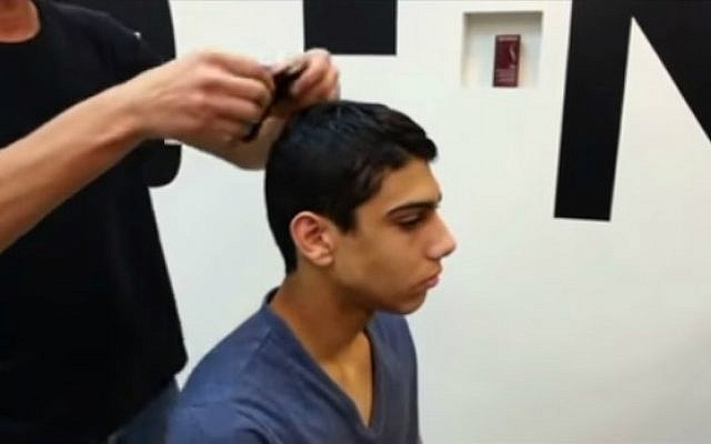 A young man gets fitted for his Magic Kippa. (YouTube screenshot)