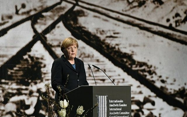 German Chancellor Angela Merkel stands in front of a historic picture of the Auschwitz concentration camp as she gives a speech during the International Auschwitz Committee's remembrance ceremony in Berlin to mark the 70th anniversary of the liberation of the Nazi death camp, on January 26, 2015. (photo credit: AFP/Tobias Schwarz)