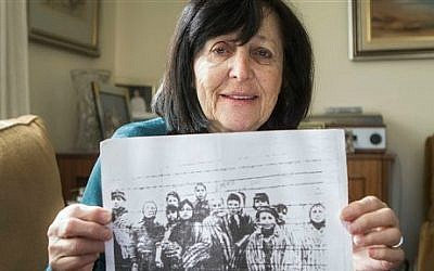 In this photo taken Thursday, Jan. 22, 2015, Marta Wise holds a famous black-and-white photo, taken by the Russian liberators of Auschwitz, showing her, center, with about a dozen children in rags standing behind a row of barbed wire (photo credit: AP/Dan Balilty)