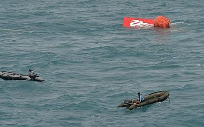 Portion of the tail of AirAsia Flight 8501 floats on the water as Indonesian navy divers conduct search operations for the black boxes of the crashed plane in the Java Sea, Indonesia, Saturday, Jan. 10, 2015 (photo credit: AP Photo/Adek Berry)