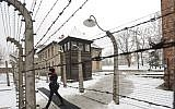 A visitor walks by barbed wire fences at the Auschwitz Nazi death camp in Oswiecim, Poland, Monday, Jan. 26, 2015. (AP/Alik Keplicz)