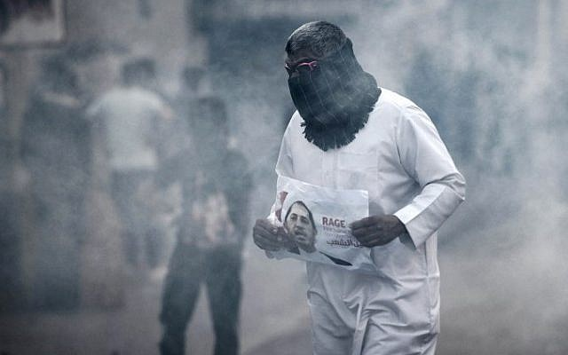 A Bahraini protestor takes cover from tear gas during clashes with riot police following a protest against the arrest of the head of the banned Shiite opposition movement Al-Wefaq, Sheikh Ali Salman (on the poster) on January 1, 2015 in Bilad al-Qadeem, a suburb of Manama. (photo credit: AFP PHOTO / MOHAMMED AL-SHAIKH)