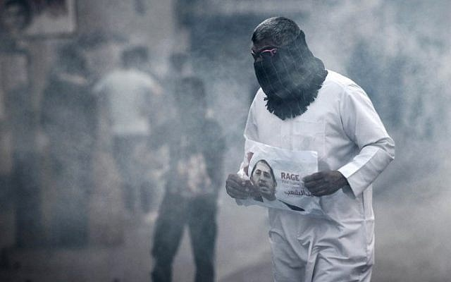 A Bahraini protestor takes cover from tear gas during clashes with riot police following a protest against the arrest of the head of the banned Shiite opposition movement Al-Wefaq, Sheikh Ali Salman (on the poster) on January 1, 2015, in Bilad al-Qadeem, a suburb of Manama. (AFP PHOTO / MOHAMMED AL-SHAIKH)