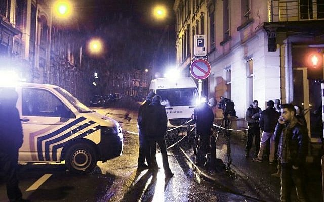 """Journalists and local residents stand near police vehicles as police set a large security perimeter in the city center of Verviers on January 15, 2015, during a """"jihadist-related"""" anti-terrorism operation. (Photo credit: AFP/ BRUNO FAHY)"""