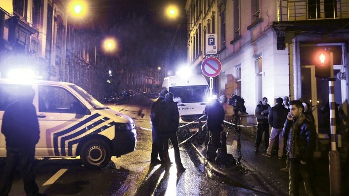 "Journalists and local residents stand near police vehicles as police set a large security perimeter in the city center of Verviers on January 15, 2015, during a ""jihadist-related"" anti-terrorism operation. (Photo credit: AFP/ BRUNO FAHY)"