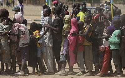 In this Thursday Nov. 27, 2014 photo, children displaced after attacks by Boko Haram, line up in the camp of internal displace people, in Yola, Nigeria. (AP Photo/Sunday Alamba, file)