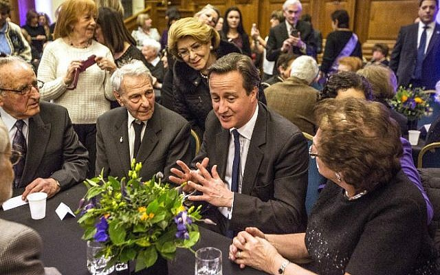 British Prime Minister David Cameron (C) talks to Holocaust survivors at a reception in the Methodist Hall in London on January 27, 2015, before the Holocaust Day memorial service in the hall (photo credit: AFP/POOL/RICHARD POHLE)