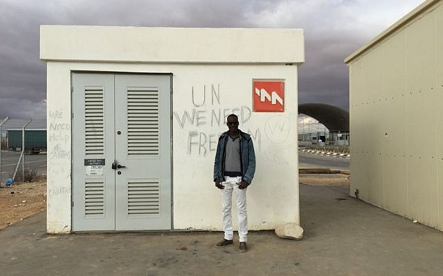 """Mutasim Ali stands in front of an electrical box at Holot, on which detainees have scrawled, """"UN We Need Freedom."""" (photo credit: Debra Kamin/Times of Israel)"""