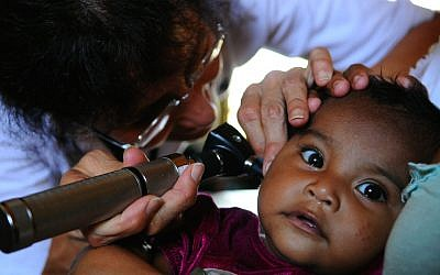 A US Navy doctor checks a infant for an ear infection during an exam at a medical clinic. (Illustrative photo credit: Courtesy US Navy/Joshua Adam Nuzzo)