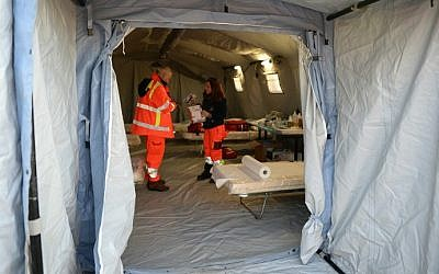 Italian Red Cross volunteers set up a tents to accommodate some 500 Syrian would-be immigrants rescued from the Ezadeen ship, on January 2, 2015 (photo credit: AFP/Alfonso Di Vincenzo)