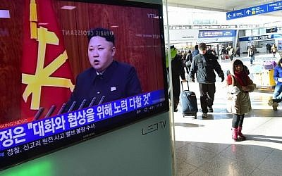 File: Travelers walk past a television screen showing North Korean leader Kim Jong Un's New Year speech, at a railroad station in Seoul on January 1, 2015. (AFP/Jung Yeon-Je)