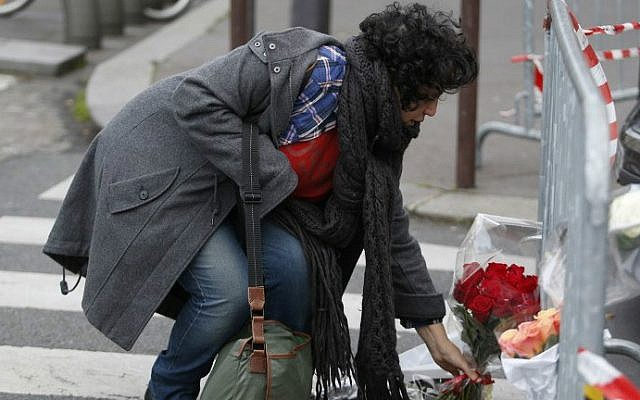 A woman lays flowers near a kosher grocery store in Porte de Vincennes, eastern Paris, on January 10, 2015 (photo credit: AFP/ KENZO TRIBOUILLARD)