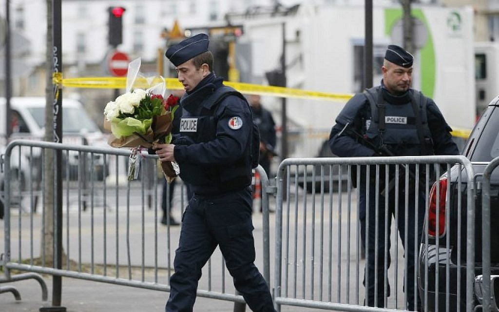 A policeman carries flowers brought by people in front of a kosher grocery store in Porte de Vincennes, eastern Paris, on January 10, 2015 (photo credit: AFP / KENZO TRIBOUILLARD)