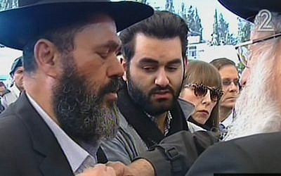 Rabbi Benjamin Hattab, the father of Yoav Hattab, who was killed in the Pairs kosher supermarket atack, rips his shirt in a Jewish sign of mourning during the funeral for his son and three other men killed in the attack, Tuesday, January 13, 2015 (screen capture: Channel 2)