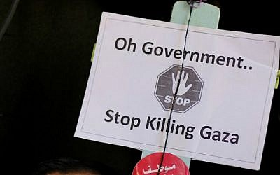 A sign held by a Palestinian employees of the former Hamas government (not pictured) during a protest at the gate of the Palestinian unity government cabinet headquarters in Gaza, January 13, 2015 (photo credit: AFP/MOHAMMED ABED)