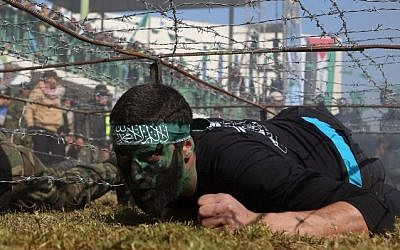 Palestinian youth crawls under a barbed wire obstacle during a graduation ceremony for a training camp run by the Hamas movement on January 29, 2015 in Khan Yunis, in the southern Gaza Strip. Photot credit: AFP/ SAID KHATIB)