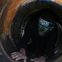 A Palestinian youth crawls in a tunnel during a graduation ceremony for a training camp run by the Hamas movement on January 29, 2015, in Khan Yunis, in the southern Gaza Strip. (AFP photo/Said Khatib)