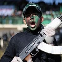 A Palestinian youth holds a weapon during a graduation ceremony as part of a training camp run by the Hamas movement on January 29, 2015 in Khan Yunis, in the southern Gaza Strip. (AFP photo/Said Khatib)