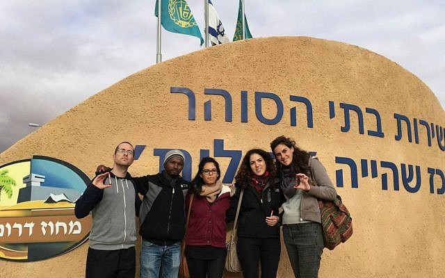 Elliot Glassenberg, far left, stands with refugees and activists at the entrance to Holot, Saturday, Jan. 17, 2015. (photo credit: Debra Kamin/Times of Israel)