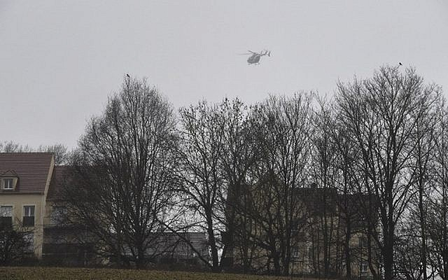 A helicopter flies over Dammartin-en-Goele, where shots were fired and at least one hostage was taken in the same area where police were hunting for the two brothers accused of slaughtering 12 people in an Islamist assault, on January 9, 2015. (photo credit: AFP/Dominique Faget)