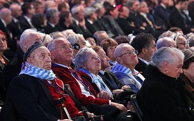 Holocaust survivors watch suspended screens in a tent raised at the entrance of the Birkenau Nazi death camp in Oswiecim, Poland, Tuesday, Jan. 27, 2015, during the official remembrance ceremony. (photo credit: AP Photo//Czarek Sokolowski)