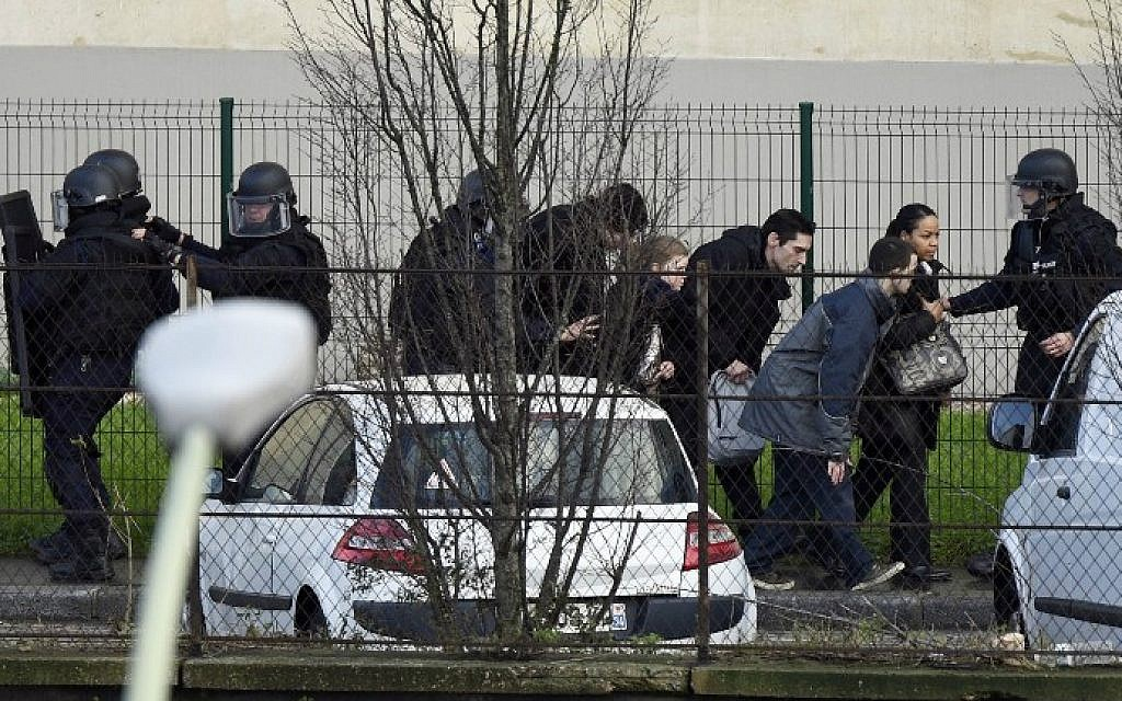 French police special forces evacuate local residents on January 9, 2015 in Saint-Mande, near Porte de Vincennes, eastern Paris, after at least one person was injured when a gunman opened fire at a kosher grocery store on January 9, 2015 and took at least five people hostage, sources told AFP. The attacker was suspected of being the same gunman who killed a policewoman in a shooting in Montrouge in southern Paris on January 8. (photo credit: AFP/ Martin Bureau)