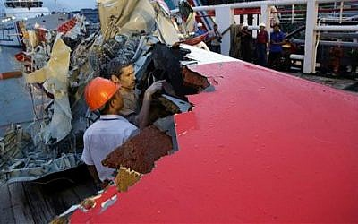 Members of the National Transportation Safety Board inspect the portion of the crashed AirAsia Flight 8501 on the deck of the rescue ship Crest Onyx at Kumai port in Pangkalan Bun, Indonesia, January 11, 2015. (photo credit: AP/Achmad Ibrahim)