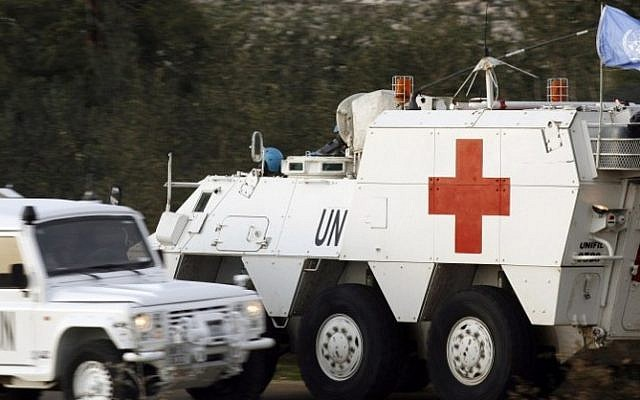 Spanish soldiers of the United Nations Interim Force in Lebanon (UNIFIL) drive an armored emergency vehicle after picking up the body of a 36-year-old UN peacekeeper from Spain who was killed as the Israeli military shelled border areas following a Hezbollah attack that left two Israeli soldiers dead. (Photo credit: AFP/MAHMOUD ZAYYAT)