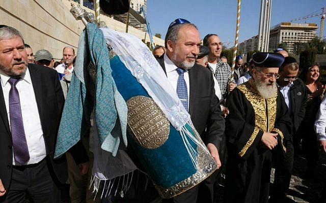 Foreign Minister Avigdor Liberman, center, and Chief Rabbi Yitzhak Yosef, right, carry a Torah scroll in the Foreign Ministry in Jerusalem, January 22, 2015 (photo credit: Elram Mandel/Foreign Ministry)