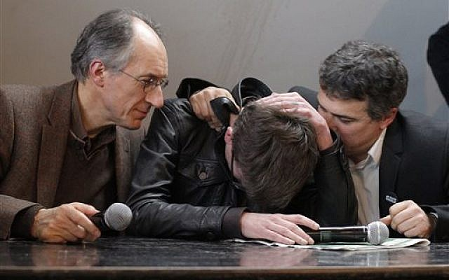 The new chief editor of French satirical magazine Charlie Hebdo, Gerard Biard, left, and columnist Patrick Pelloux, right, comfort cartoonist Luz during a press conference in Paris, France, Tuesday, Jan. 13, 2015. (AP Photo/Christophe Ena)