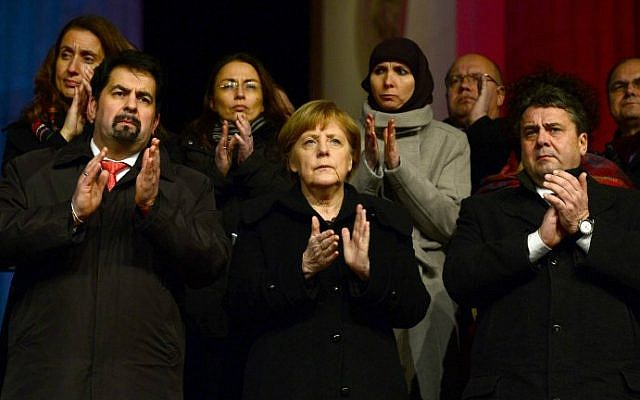 German Chancellor Angela Merkel (center) applauds during a Muslim community tolerance rally on January 13, 2015 in Berlin (photo credit: AFP/JOHN MACDOUGALL)