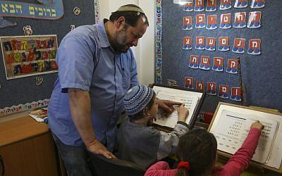 Rabbi Eran Fletzki teaches children at a school in the West Bank settlement of Neve Daniel, Nov. 25, 2013. (Photo credit: Nati Shohat/Flash90)