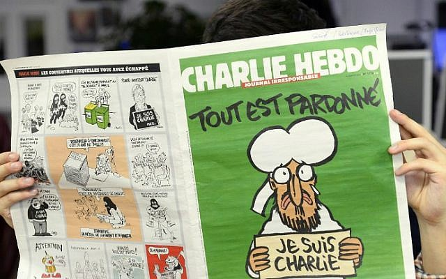 A man reads, in a newsroom in Paris, the latest issue of French satirical weekly Charlie Hebdo on January 13, 2015 (photo credit: AFP/Bertrand Guay)