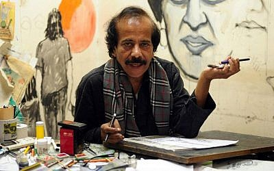 """In this photograph taken on January 9, 2015, Pakistani cartoonist Rafique Ahmad, alias """"FEICA"""" draws at his office in Karachi. In the face of Pakistan's prolific use of blasphemy laws and a culture of political violence, cartoonists must tread a thin line (photo credit: AFP / Asif Hassan)"""