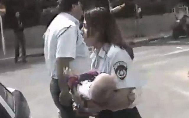 Policewoman Ziona Busheri retrieves 6-month-old Shani Winter from the Cafe Apropos blast in Tel Aviv, March 1997. (screen capture: Channel 2)