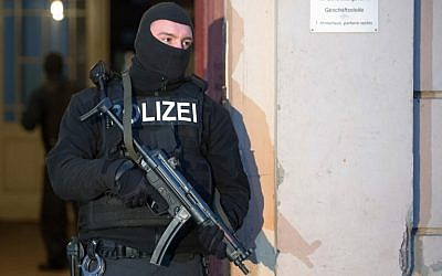 Illustrative: A member of a police task force stands in front of an apartment building where raids took place against suspected jihadists on January 16, 2015 in Berlin (photo credit: AFP/ LUKAS SCHULZE)