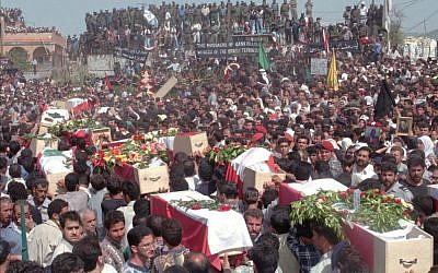 Mourners carry coffins draped in Lebanese flags as they arrive in the southern Lebanese village of Qana Tuesday, April 30, 1996 to bury 91 victims in a mass grave beside the UN post in which they were killed by Israeli shells on April 18. (photo credit: AP Photo/Ali Mohamed)