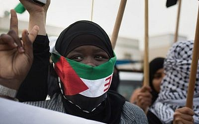 A Bedouin woman, covering her face with a Palestinian flag, marches with fellow protesters ahead of the funeral of Sami al-Zayadna, 47, in the southern Israeli Bedouin city of Rahat on January 19, 2015. Zayadna died the previous day following clashes with Israeli policemen during the funeral of Sami al-Ajar, 22, another Bedouin who died of a gunshot wound last week during a police drug raid on the Negev Bedouin town. (Photo credit: AFP/MENAHEM KAHANA)