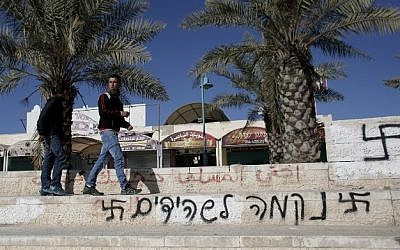 "Graffiti reading in Hebrew: "" Revenge for the shahids (martyrs)"" flanked by two swastikas, is pictured on a wall in the southern Israeli Bedouin city of Rahat on January 20 2015.  (Photo credit: AFP / AHMAD GHARABLI)"
