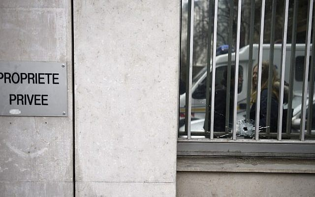 A bullet hole in the window of the offices of the French satirical newspaper Charlie Hebdo in Paris, after armed gunmen stormed the offices leaving 11 people dead on January 7, 2015. (Photo credit: AFP/ MARTIN BUREAU)