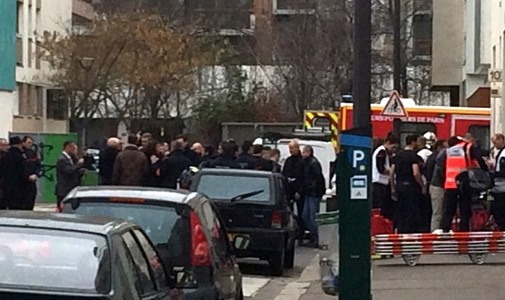 Firefighters and police officers gather in front of the offices of the French satirical newspaper Charlie Hebdo in Paris on January 7, 2015, after armed gunmen stormed the offices leaving 11 dead. (Photo credit: AFP/ PHILIPPE DUPEYRAT)