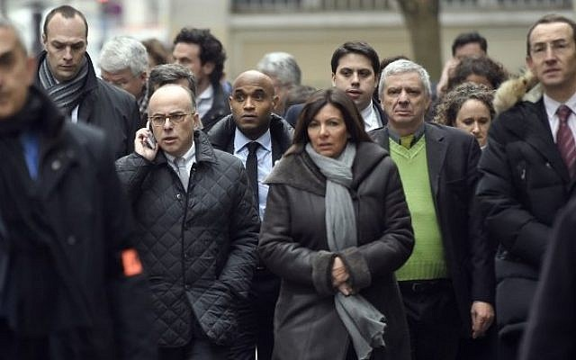 France's interior minister Bernard Cazeneuve (C, L) and Paris' Mayor Anne Hidalgo (C, R) arrive at the headquarters of the French satirical newspaper Charlie Hebdo in Paris on January 7, 2015, after armed gunmen stormed the offices leaving at least 11 people dead. (Photo credit: AFP/ MARTIN BUREAU)