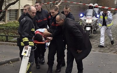 A victim is evacuated on a stretcher on January 7, 2015 after armed gunmen stormed the offices of the French satirical newspaper Charlie Hebdo in Paris, leaving 12 people dead. (Photo credit: AFP/ MARTIN BUREAU)