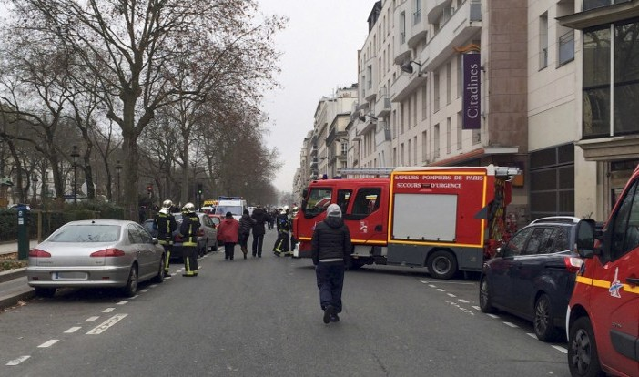 Firefighters and rescue services gather near the offices of the French satirical newspaper Charlie Hebdo in Paris on January 7, 2015, after armed gunmen stormed the offices leaving 12 dead, including two police officers, according to sources close to the investigation. (Photo credit: AFP/ PHILIPPE DUPEYRAT)