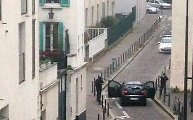 Armed gunmen face police officers near the offices of the French satirical newspaper Charlie Hebdo in Paris on January 7, 2015, during an attack on the offices of the newspaper which left 12 dead. (Photo credit: AFP/ ANNE GELBARD)
