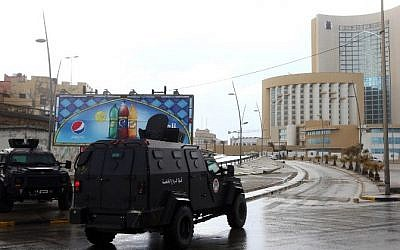 Libyan security forces and emergency services surround Tripoli's central Corinthia Hotel (R) on January 27, 2015 in the Libyan capital. The hotel was reportedly attacked by Islamist gunmen. (Photo credit: AFP/MAHMUD TURKIA)